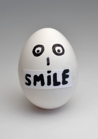 pasted: Egg with the pasted inscription smile instead of a mouth Stock Photo