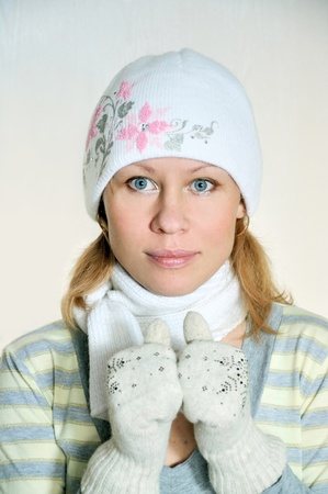 The beautiful girl in the winter in a cap, gloves, and a scarf photo