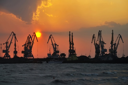 distant work: Port cranes at sea at the setting sun (at the end of the day)