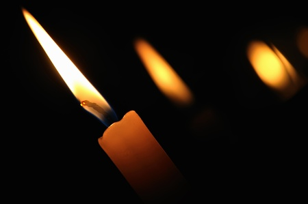 A burning candle in the church on a dark background photo