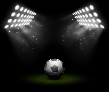投光器の光の中のサッカー ボール