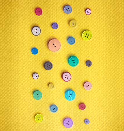 Colorful Annähen von Knöpfen auf gelbem Hintergrund. Illustration