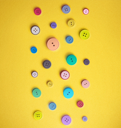 Colorful sewing buttons on yellow background.
