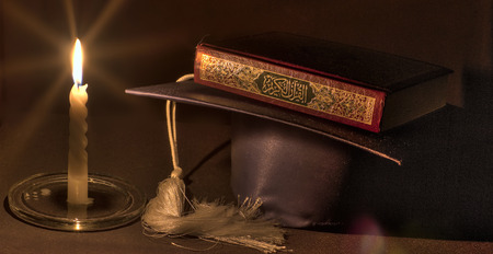 Still life composed of Quran (Koran) placed on a graduation cap and lighted using a candle alone. 版權商用圖片 - 86759317