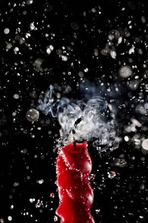 High speed shot for water being sprinkled over a lighted red candle. Part of series.
