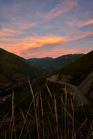 Beautiful sunset in the mountains south of Asturias with the road and orange mountains in vertical, Spain