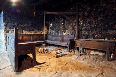Ancient kitchen of more than 300 years with its pot hanging from a wooden arch and chains to make the fire with a bench around it, a stool and a bread basket where the bread was fermented