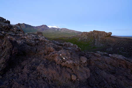 Beautiful view of saxholl crater with rocks in the foreground and with the Snæfellsjökull glacier in the distance on the island of Iceland