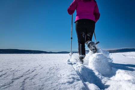 Healthy middle-aged woman snowshoeing on a sunny winter afternoon .