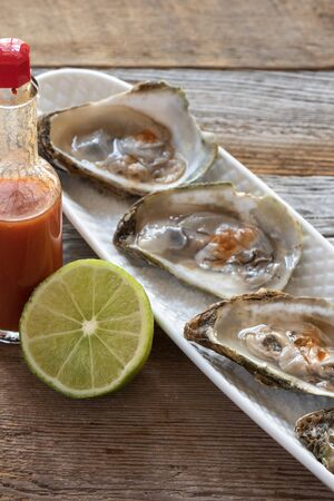 Delicious raw East Coast oysters with lime and hot sauce.