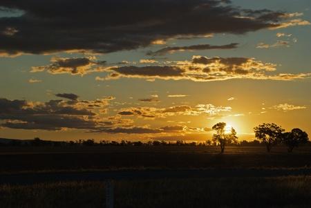 a rich rural sunset across farm paddock photo