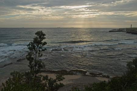 cargo ships on the horizon as waves roll into shore Stock Photo - 13135160