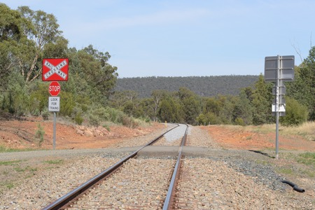 a railway line crossing in rural australia with hill and trees photo