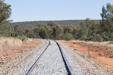 ballast: railway line curves around a bend with new ballast and trees Stock Photo