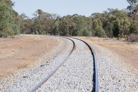 ballast: a railway line curves around trees with new ballast and blue sky