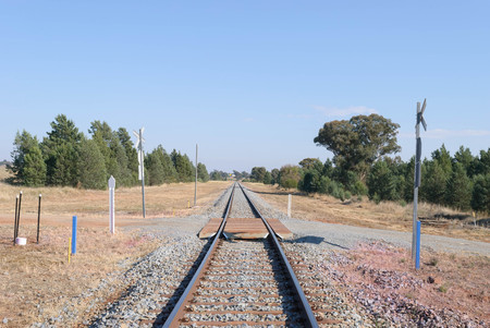 long straight railway line with a railway crossing close with trees on a sunny day