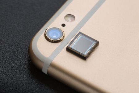 cmos: A piece of CMOS placed next to a mobile phone camera. Stock Photo