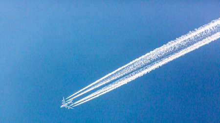 Four engined airplane during flight with condensation trails