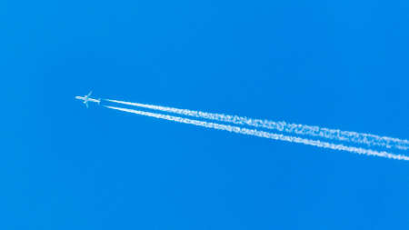 Two engined airplane during flight with condensation trails