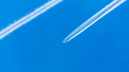 Two engined airplane during flight with condensation trails Banque d'images