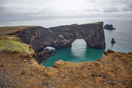 View on natural arches at Reynisfjara black beach in southern Iceland in summer