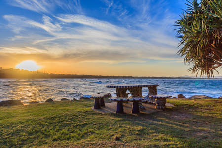 Photo of a sunset by the sea with seating in the foreground photogriert in March 2015 Archivio Fotografico