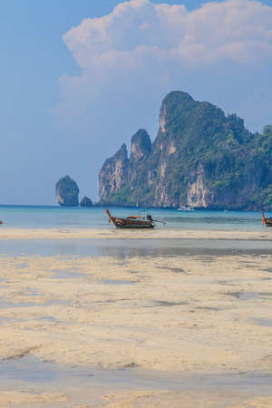 Photo of a boat stranded at low tide on the island of Phi Phi Island with large rocks in the background during the day in cloudless skies photographed in Thailand in November 2013 Archivio Fotografico