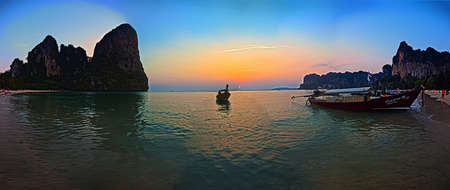 Panoramic shot of the sunset at Railay Beach in Krabi in cloudless sky framed by rocks and with typical longtail boat in the foreground photographed in Thailand in November 2013