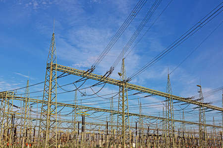 Picture of a transformer station with many insulators and cables during the day in front of a blue sky