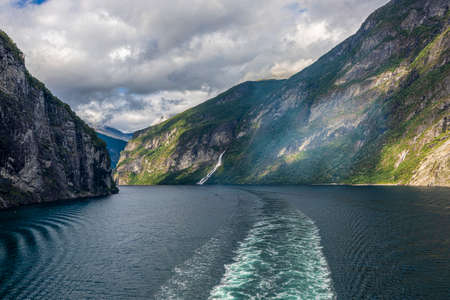 Impression from cruise ship on the way through Geiranger fjord in Norway at sunrise