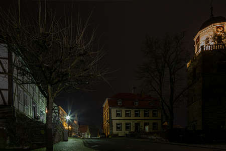 Night scene of an old German town with studwork houses and cobbled street in wet weather during wintertime