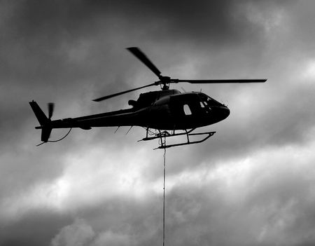 Small Helicopter Silhouette with Sling Load During Longline Operations Stok Fotoğraf