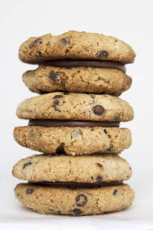 Stack of delicious italian sandwich cookies Baci di Dama or Ladys Kisses made with hazelnut flour, chocolate chips and filled with gianduja spread on white background. Sweet food, Piedmont speciality Banco de Imagens - 127529437