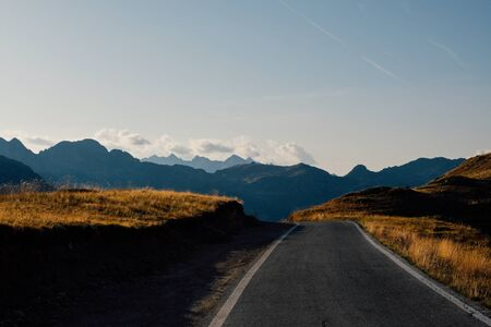 Beautiful landscape with road and mountain range silhouette in the Alps during sunset