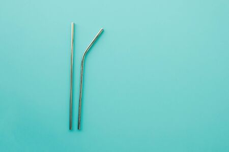 Reusable eco friendly metallic straws on trendy mint background. Flat lay, top view. Space for text. Zero waste and sustainable lifestyle concept.