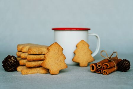 Stack of delicious homemade shortbread cookies in the shape of Christmas tree and cup of hot drink. Stock Photo