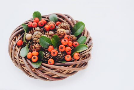 Beautiful wooden Christmas wreath made of willow branches with pine cones and red cotoneaster berries on white wooden background. Space for text. Zero waste holiday concept.