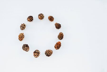 Beautiful eco friendly Christmas wreath made with pine cones on white background. Creative plastic free festive garland, top view, flat lay, minimal style. Space for text. Zero waste holiday concept. Banco de Imagens