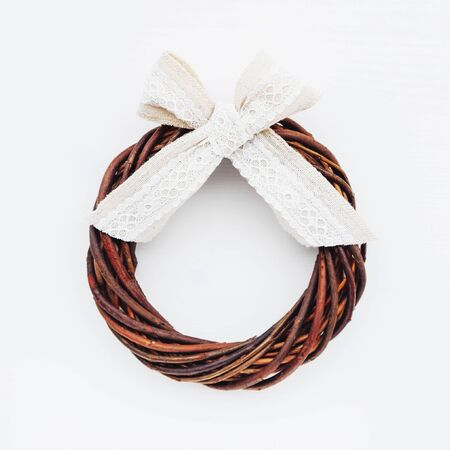 Lovely eco friendly minimalist Christmas wreath made of willow branches with cotton ribbon on white