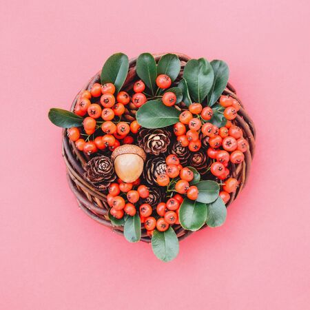 Natural eco friendly Christmas wreath on red background. Creative plastic free pretty festive garland, top view, flat lay style. Zero waste holiday concept. Stock Photo
