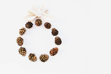 Beautiful eco friendly Christmas wreath made with pine cones and cotton ribbon on white background. Creative festive garland, top view, minimal style. Space for text. Zero waste holiday concept. Stock Photo
