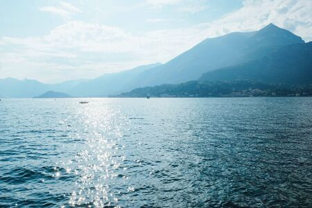 Beautiful view of Como Lake or Lago di Como, popular tourist attraction in Lombardy, Northern Italy. Copy space. Summer vacations concept. Water surface with sun glare. Banco de Imagens