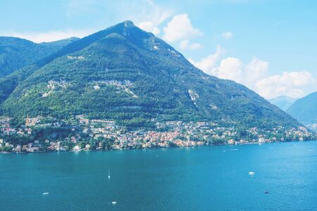 Beautiful view of Como Lake or Lago di Como in summer. Popular tourist attraction in Lombardy, Northern Italy. Summer vacations concept.