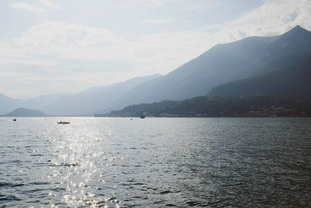 Beautiful mountain landscape with Como Lake or Lago di Como, popular tourist attraction in Lombardy, Northern Italy. Copy space. Summer vacations concept. Water surface with sun glare, evening light. Banco de Imagens