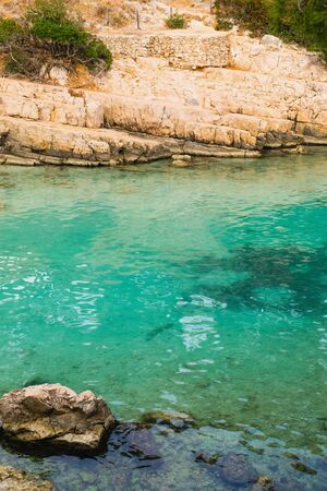 Beautiful wild beach with turquoise water and rocky cliffs in Calanques National Park, Cassis. Popular nature attraction in Southern France.