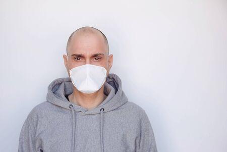 Concept de quarantaine, de maladie et d'isolement à domicile. Nouveau coronavirus, pandémie de COVID-19. Jeune homme portant un masque médical de protection sur fond blanc. Espace pour le texte