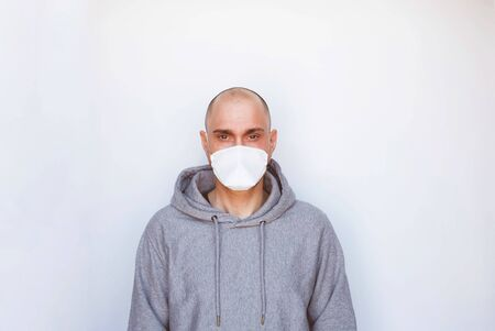 Quarantine, sickness and home isolation concept. Novel Coronavirus, COVID-19 pandemic. Young man wearing protective medical mask against white background. Space for text. 免版税图像