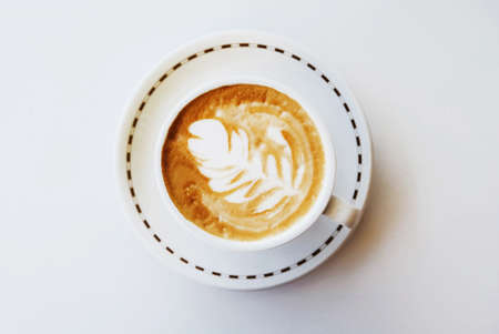 A cup of fresh delicious cappuccino coffee with latte art in the shape of leaf on white background, top view. Space for text.