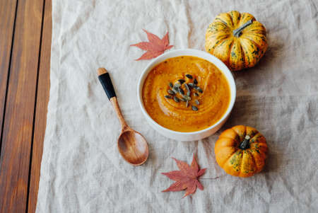 Hot pumpkin soup served with squash seeds in a bowl.