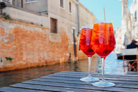 Two glasses of Spritz Veneziano cocktail served near the Venetian canal. Popular italian summer aperitif drink. Place for text.